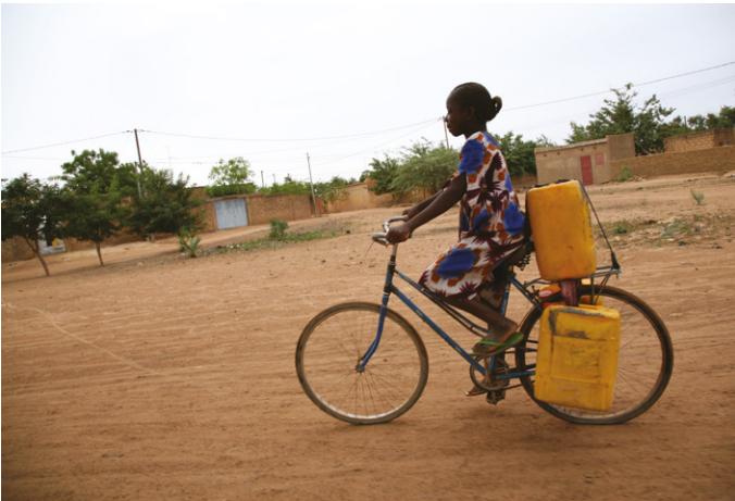 Burkina Faso- Une femme à vélo transporte de l'eau d'un point de distribution à son ménage